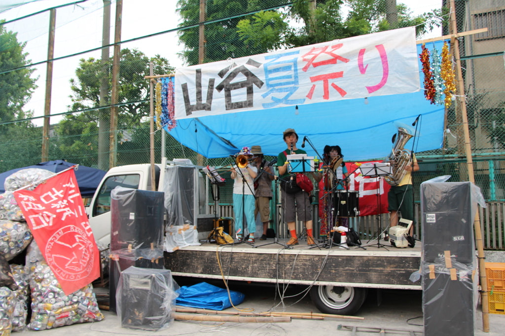 Jinta-la-Mvta performing at a summer festival in Sanya, an old day laborer's neighborhood in Tokyo. The band on stage (clarinet, trombone, tuba, drums)