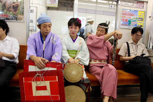 Chindon Tsūshinsha taking the train on their way to a gig. From left: Hirabayashi, Nao (p. 75, 122), and Kobayashi (pp.119-120).