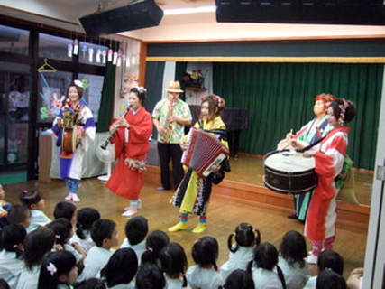 Chindon-ya has been employed by kindergarten classes. A troupe performs at a school, in front of a seated audience of kindergarten students.