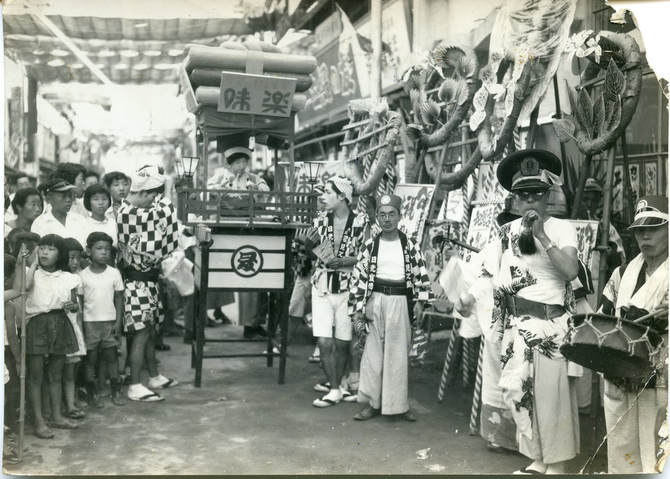 Black and white photograph. Nikko Sendensha, Ikuno Ward, Osaka, circa 1940. A chindon-ya troupe prepares, surrounded by children and onlookers.