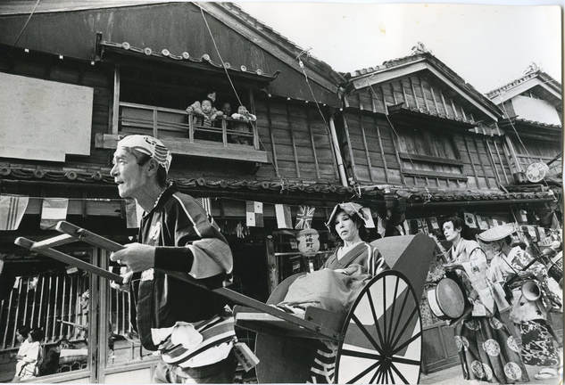 Black and white photograph of Shumei Koogeisha, circa 1960. The performer pulls a woman in an illustrated