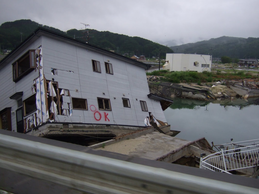 Four months after the tsunami and earthquake 2011; a house has fallen into a bay at an angle.